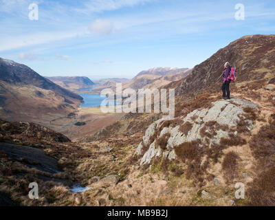 Female hiker admires view from Little Round How, Fleetwith Pike along Warnscale Bottom to Buttermere, with Mellbreak rising over Crummock Water beyond - Stock Photo