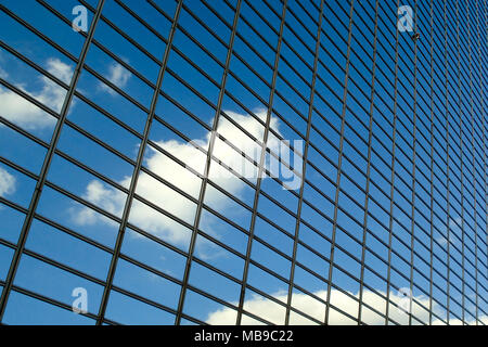 Blue sky with clouds reflections on a modern glass business building - Stock Photo
