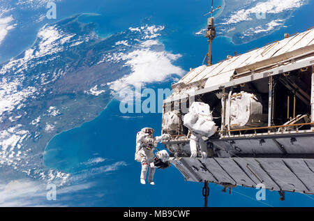 INTERNATIONAL SPACE STATION  Astronauts working on the constuction of the Integrated Truss Structure section on 12 December 2006. The North and South islands of New Zealand are below them. - Stock Photo