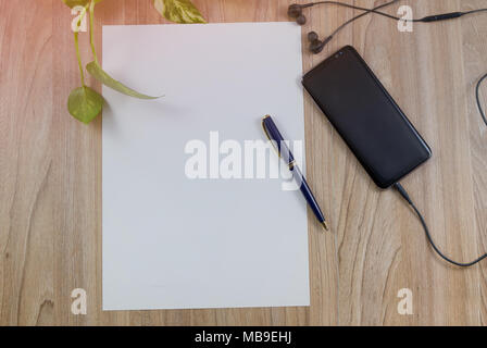 Smartphone, Cell phone, earphone, white paper and pen on wood table top view with copy space, flat lay background - Stock Photo