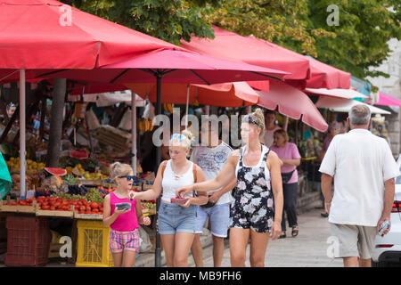 Mother and two daughters eating berries at the market of Zadar, Croatia - Stock Photo