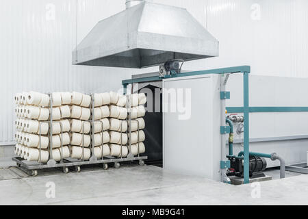 trolley with finished products in the drying room at the textile factory - Stock Photo