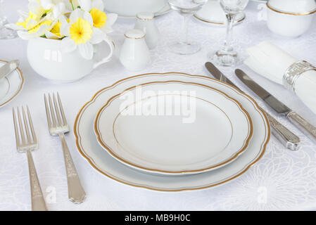 Classic serving for a gala dinner with luxurious porcelain, silverware and spring flowers on a white tablecloth - Stock Photo