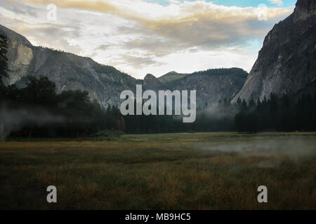 Beautiful morning hour over a meadow in yosemite valley featuring the world famous rock-climbing rocks El Capitan and Half dome - Stock Photo