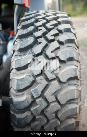 Heavy duty rubber tire with deep treads on an all-terrain 4x4 off road vehicle on a dirt road in a close up view - Stock Photo