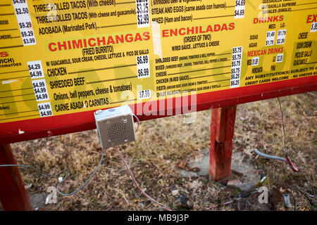 Prices and dishes on a yellow outdoor menu board advertising Mexican cuisine in a close up view - Stock Photo