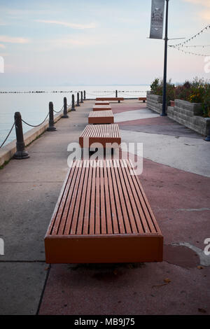 Row of empty benches on the Navy Pier, Chicago, Illinois receding along the promenade overlooking the ocean - Stock Photo