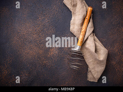 Vintage wooden whisk on old rusty background  - Stock Photo