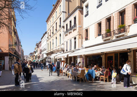 Busy street scene on Strada Nova, Cannaregio, Venice, Veneto, Italy with people eating at restaurants and shopping in the shops and stores in spring - Stock Photo