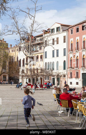 Campo San Polo, San Polo, Venice, Veneto, Italy in spring with a little girl chasing birds and people dining at a restaurant  and relaxing on benches  - Stock Photo