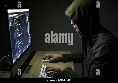Hooded computer hacker stealing information with pc. Dark background - Stock Photo