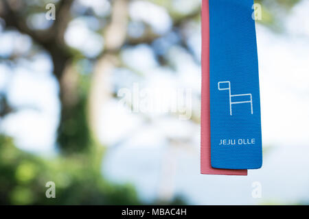 Jeju Olle ribbon as marker for trekking trails with tree in the back, Seogwipo, Jeju Island, South Korea - Stock Photo