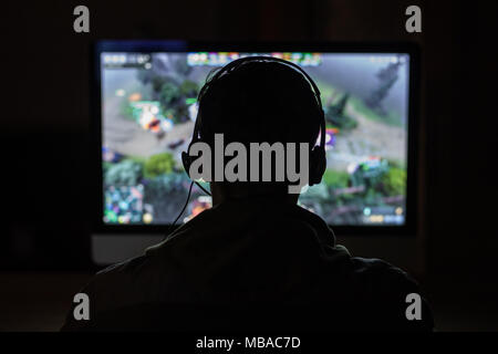 Back view of concentrated young gamer in headphones and glasses using computer for playing game at home - Stock Photo