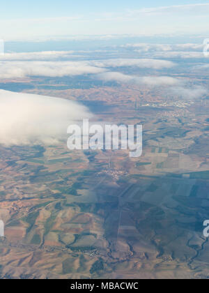 Aerial view of the Madrid region, outside the metropolitan area. Flying over agricultural fields and clouds. Spain - Stock Photo