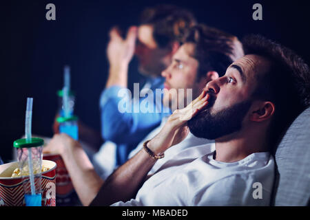 Group of happy friends sitting in cinema watch film and eating popcorn - Stock Photo