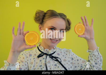 beautiful funny young girl holding slices of oranges in hands on bright background - Stock Photo