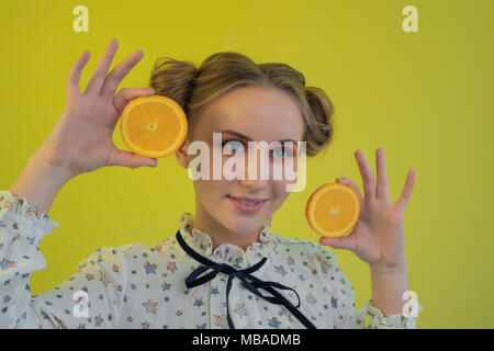 Portrait of a blonde girl with a funny hairdo and in a light shirt holding slices of oranges posing against a bright background - Stock Photo