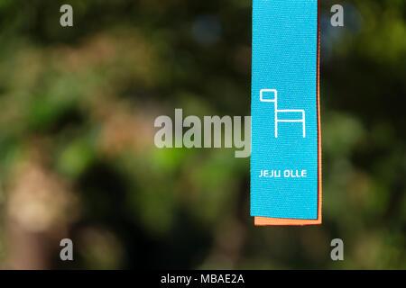 Jeju Olle ribbon in front of green leaf bokeh as marker for trekking trails, Seogwipo, Jeju Island, South Korea - Stock Photo