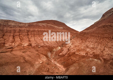 Red striped mountains at overcast sky in desert park Altyn Emel in Kazakhstan - Stock Photo