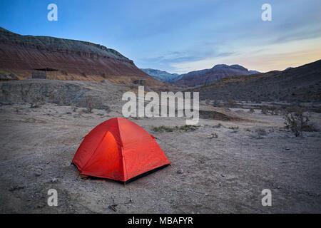 Touristic orange tent in the Desert mountains at sunrise in Kazakhstan - Stock Photo