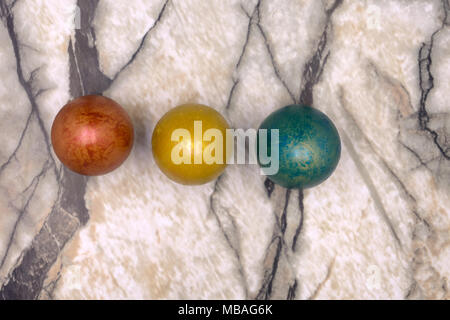 Colorful bright Easter little eggs lined up in the middle of picture, made of plasticine on wooden blurry background with blue, orange, yellow, green  - Stock Photo
