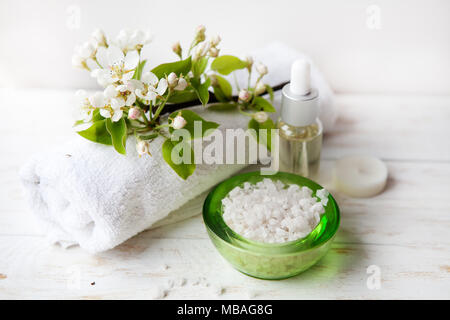 Spa set with sea salt,  flowers and candles on wicker tray. Massage oil, towel, sea salt and candles - Stock Photo