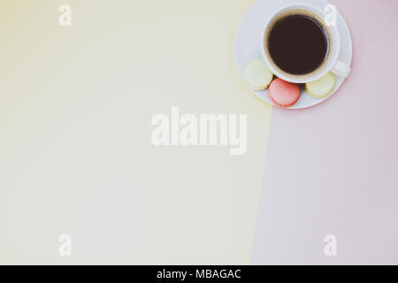 Creative flat lay photo of coffee cup and macaroons with copy space on pink and yellow background minimal style