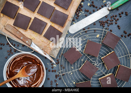 Caramel shortbread / Millionaires shortbread squares with a pallet knife and melted dark chocolate in a bowl on a slate background - Stock Photo