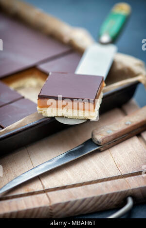 Caramel shortbread / Millionaires shortbread square on a pallet knife on a wooden chopping board - Stock Photo