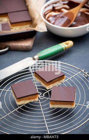 Caramel shortbread / Millionaires shortbread squares with a pallet knife on a round vintage wire cooling rack on a slate background - Stock Photo