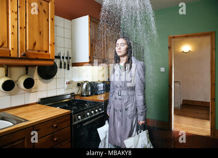 Woman standing in kitchen under shower of rain, indoors - Stock Photo