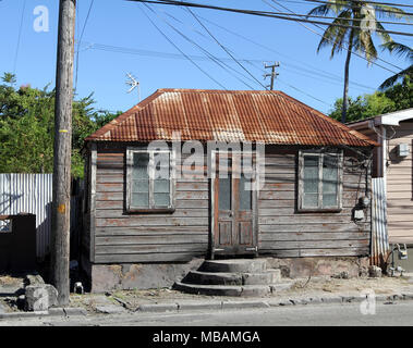 rustic Caribbean style house architecture with rusty corrugated sheet metal roof, peeling painted wooden siding and rounded step entrance - Stock Photo