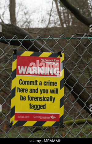 Network Rail warning sign near a railway stating Commit a crime here and you will be forensically tagged - Stock Photo