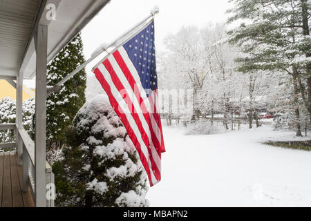 Luxury Suburban Home Flies an American Flag  in Snowstorm, New England, USA - Stock Photo