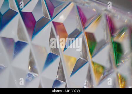 Macro abstract view of diamond shape facet designs cut into beautiful lead crystal glassware reflecting various colors of light - Stock Photo