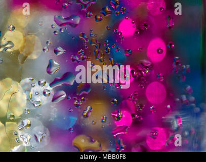 Whimsical abstract created with macro photographed water droplets on glass with multi color bokeh in background - Stock Photo