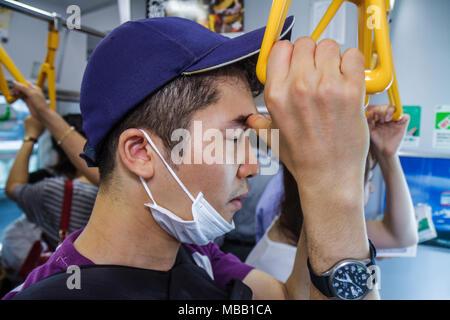 Tokyo Japan Yurakucho JR Yurakucho Station Yamanote Line Asian man crowded standing commuters train car strap holders nodding of - Stock Photo