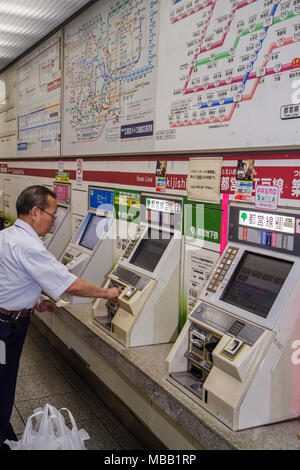 Tokyo Japan Tsukiji Oedo Line Tsukishima Station ticket adjustment vending machine train subway route map Asian man buying kanji - Stock Photo