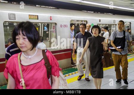 Tokyo Japan Tsukiji Oedo Line Tsukishima Station train subway Asian man woman commuters arriving transferring - Stock Photo