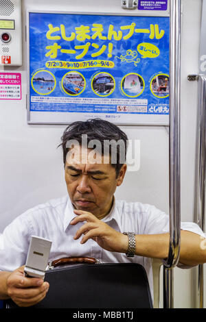 Tokyo Japan Tsukiji Oedo Line Tsukishima Station train subway car kanji hiragana characters Japanese and English Asian man commu - Stock Photo
