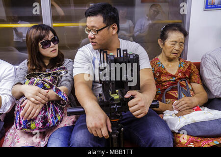 Tokyo Japan Tsukiji Oedo Line Tsukishima Station train subway car Asian man large format camera woman senior nodding off dozing - Stock Photo