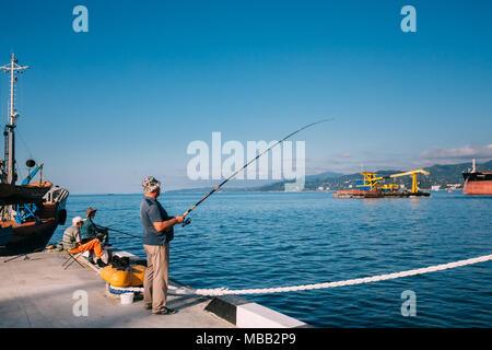Batumi, Adjara, Georgia - September 10, 2017: Old Man Fishing Near Port Dock On Sunny Evening At Sunset Time In Batumi, Adjara, Georgia - Stock Photo