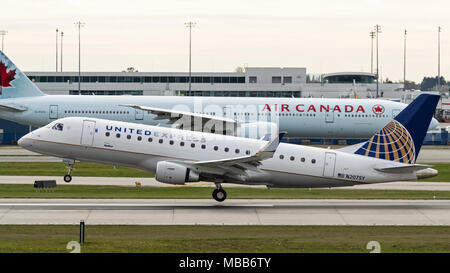 Richmond, British Columbia, Canada. 3rd Nov, 2017. A United Express Embraer E175 (N207SY) narrow-body single-aisle twin-engine jet airliner, operated by SkyWest Airlines, takes off from Vancouver International Airport. In the background an Air Canada Boeing 777-300ER (C-FIVX) taxies along the tarmac. Credit: Bayne Stanley/ZUMA Wire/Alamy Live News - Stock Photo