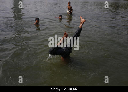 Dhaka, Bangladesh. 10th Apr, 2018. Children take bath in a lake on a hot weather day in Suhrawardy Udyan. Credit: Md. Mehedi Hasan/ZUMA Wire/Alamy Live News - Stock Photo