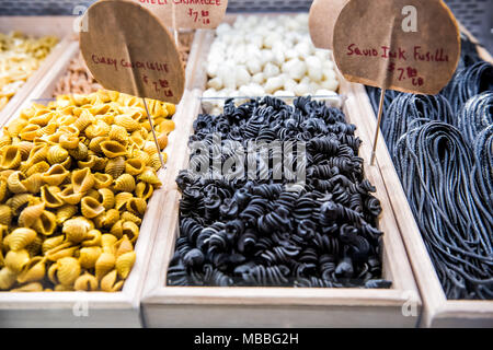 Closeup of black squid ink spiral fusilli pasta noodles fresh raw uncooked charcoal in italian gourmet market, signs for curry conchiglie shells - Stock Photo