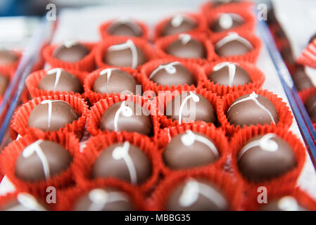 Shiny smooth gourmet milk and white chocolate brandy alcoholic truffles on a tray in bakery chocolatier candy shop store display - Stock Photo
