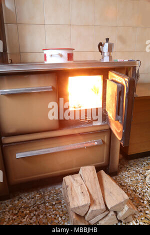 fire of and old stove in the kitchen of a mountain chalet - Stock Photo