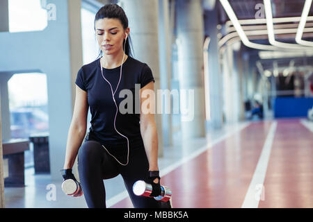 girl doing lunges with dumbbells in gym. female athlete doing split squats - Stock Photo