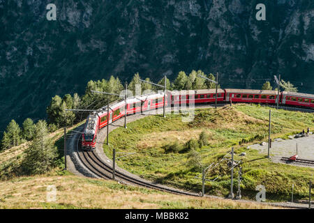 Bernina Express at Alp Gruem, with the Valposchiavo in the background, Engadin, Switzerland | Bergzug an der Alp Gruem Zugstation mit dem Puschlav Tal - Stock Photo