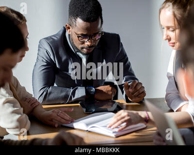 Business people listening to marketing professional african speaker presentation - Stock Photo